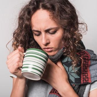 Primer plano de mujer joven bebiendo café de la taza