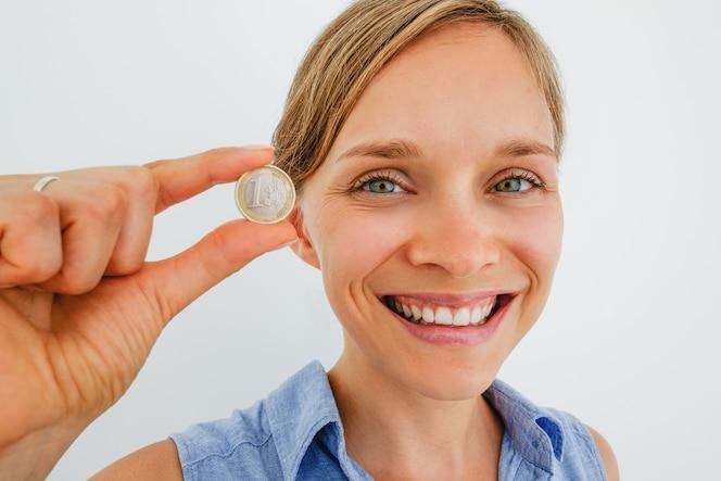 Primer plano de mujer sonriente sosteniendo una moneda de euro