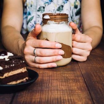 Primer plano de mujer sosteniendo el batido de chocolate en el vaso en la mesa de madera