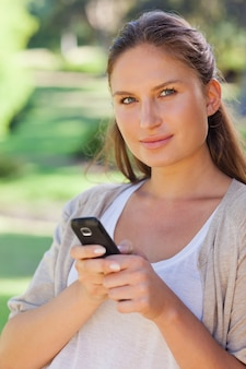 Primer plano de mujer sosteniendo su teléfono celular en el parque