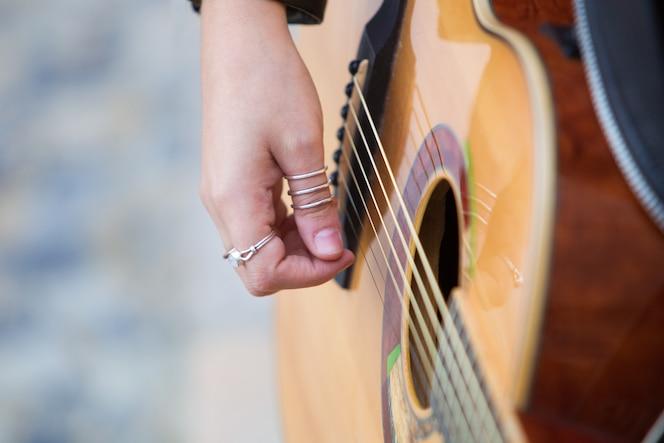 Primer plano de mujer tocando la guitarra acústica