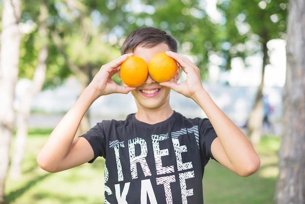 Primer plano de niño cubriéndose los ojos con naranjas