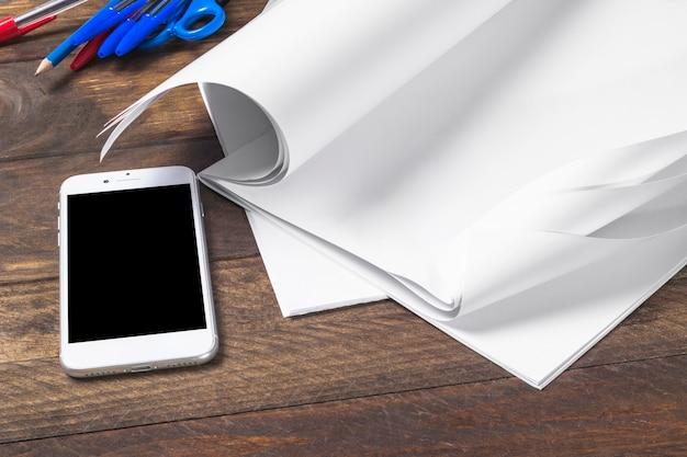Primer plano de papel en blanco blanco con teléfono móvil sobre la mesa de madera