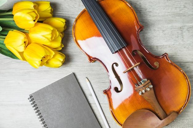 Primer plano de tulipanes; diario; lápiz y violín sobre fondo de madera