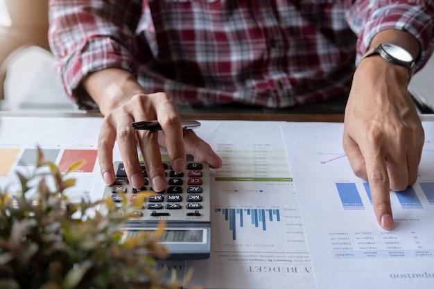 Primer plano de un especialista financiero empresario está trabajando con la calculadora y la computadora