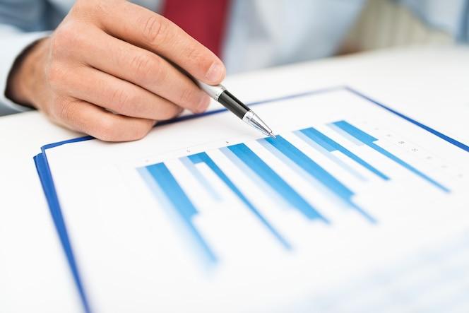 Primer plano de un hombre de negocios analizando un documento comercial
