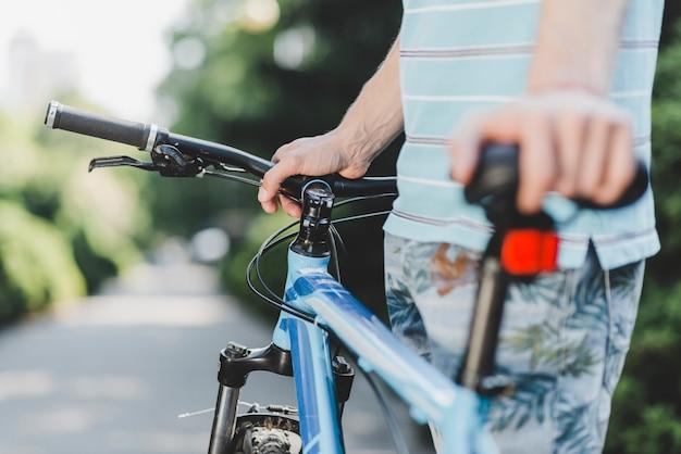 Primer plano, de, un, hombre de pie, con, bicicleta, en, aire libre