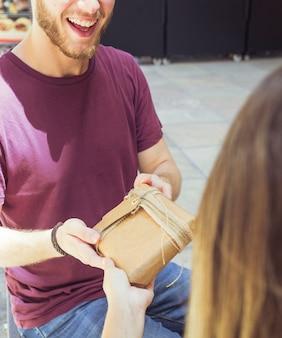 Primer plano de un hombre feliz dando un regalo a su novia