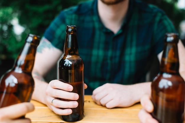 Primer plano de un hombre que sostiene la botella de cerveza marrón con sus amigos