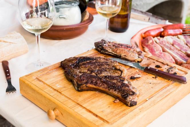 Primer plano de una carne cocida y un cuchillo en la tabla de cortar de madera