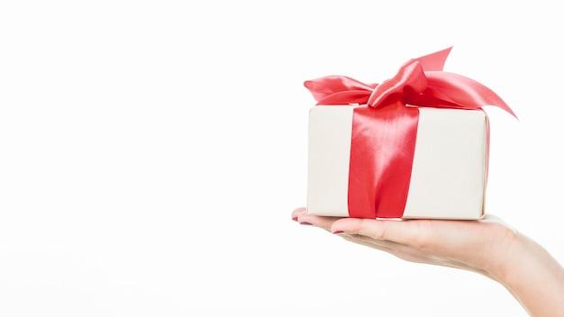 Primer plano de una mano de mujer con regalo sobre fondo blanco