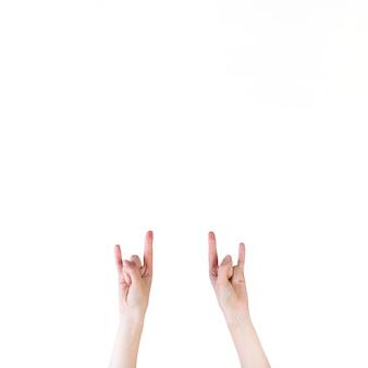 Primer plano de una mano humana haciendo señal de rock sobre fondo blanco