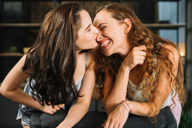 Primer plano de una mujer besando la nariz de su novia feliz