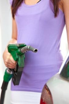Primer plano de una mujer de reabastecimiento de combustible de su coche
