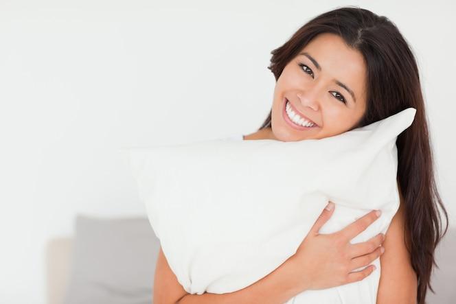 Primer plano de una mujer encantadora con almohada sentada en su cama mirando a cámara