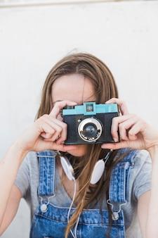Primer plano de una mujer haciendo clic en la fotografía con la cámara