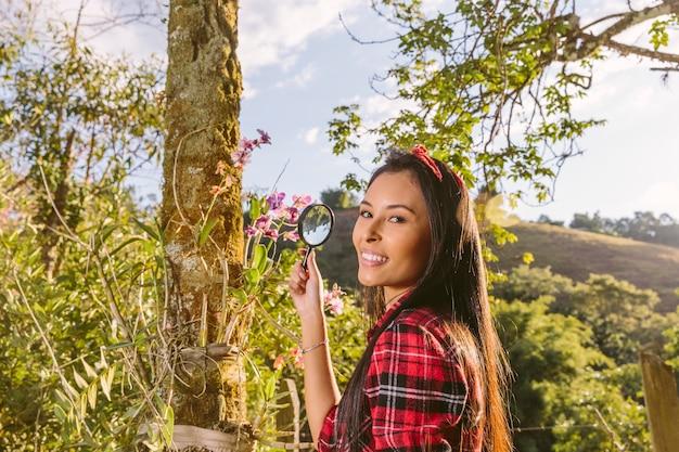 Primer plano de una mujer joven feliz con lupa