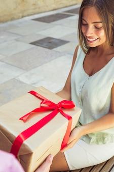 Primer plano de una mujer joven feliz recibiendo regalos