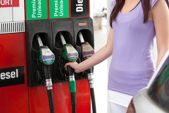 Primer plano de una mujer joven reabastecimiento de combustible de su coche