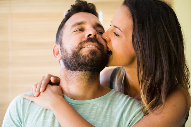 Primer plano de una mujer mordiendo la mejilla de su marido