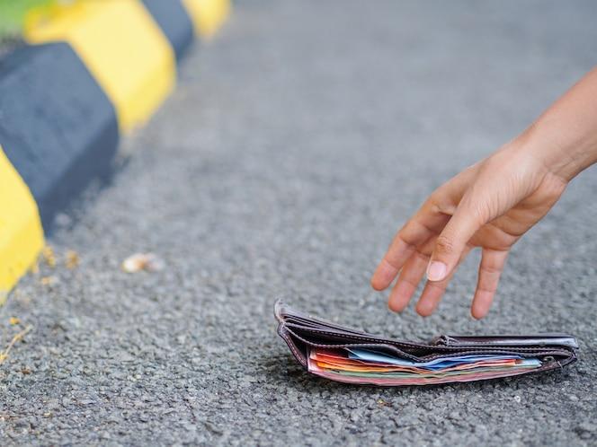 Primer plano de una mujer recogiendo billetera caída en el lado de la carretera