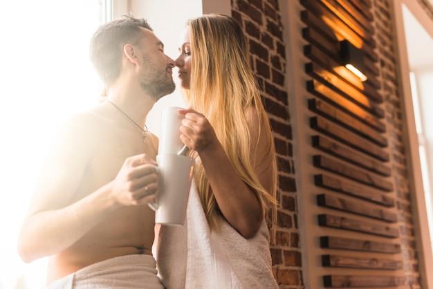 Primer plano de una pareja joven con taza de café besándose