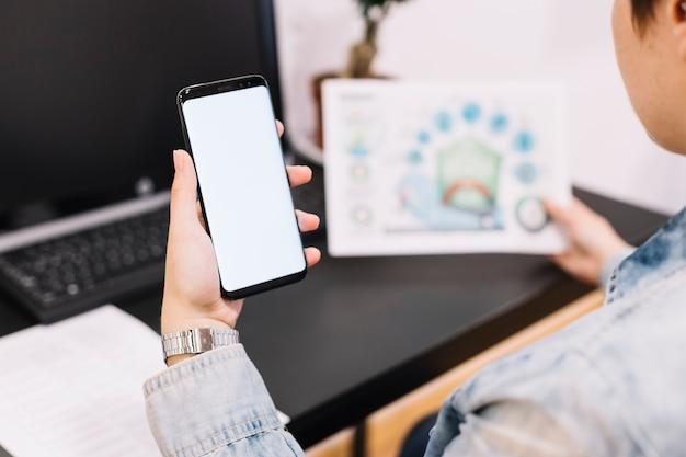 Primer plano de una persona que sostiene el teléfono móvil con pantalla en blanco en el lugar de trabajo