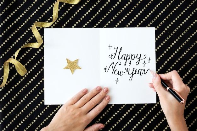 Primer plano de vista aérea de la mano escribiendo deseo de año nuevo en la tarjeta