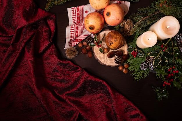 Primer plano de una decoración navideña con velas pino rama conos frutas y panettone