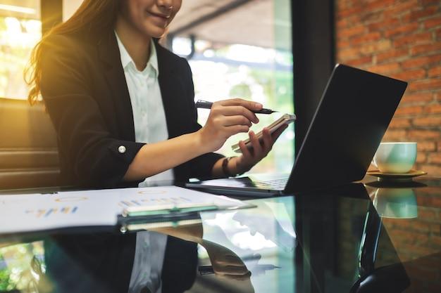 Primer plano del dedo acusador de la empresaria en la computadora portátil mientras trabajaba en la oficina