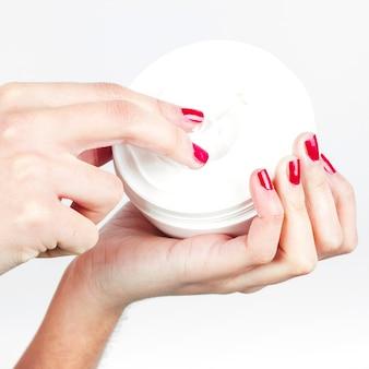 Primer plano de dedo de mujer aplicando crema hidratante.