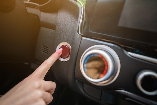 Primer plano de un dedo de una mujer presionando el botón de luces de emergencia mientras conduce. detalle en el salpicadero del coche.