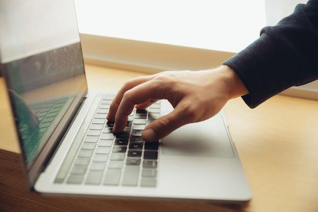 Primer plano de los dedos masculinos escribiendo un documento comercial, una nota o una tecla de búsqueda en la computadora portátil