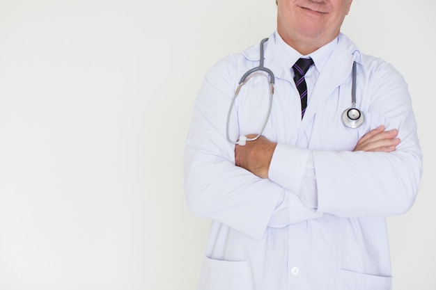 Primer plano del contenido doctor maduro con los brazos cruzados