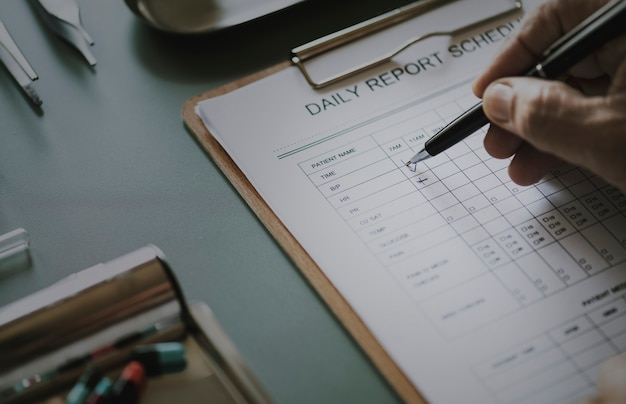 Primer plano del doctor revisando la lista de verificación del informe diario del paciente