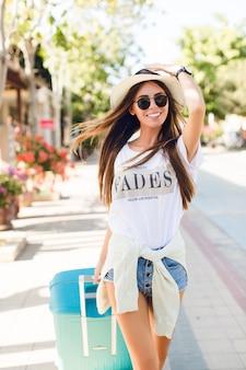 Primer plano de delgada joven bronceada caminando en un parque con maleta azul detrás de ella. lleva pantalones cortos de mezclilla, camiseta blanca, sombrero de paja y gafas de sol oscuras. ella sonríe y sostiene su sombrero con una mano