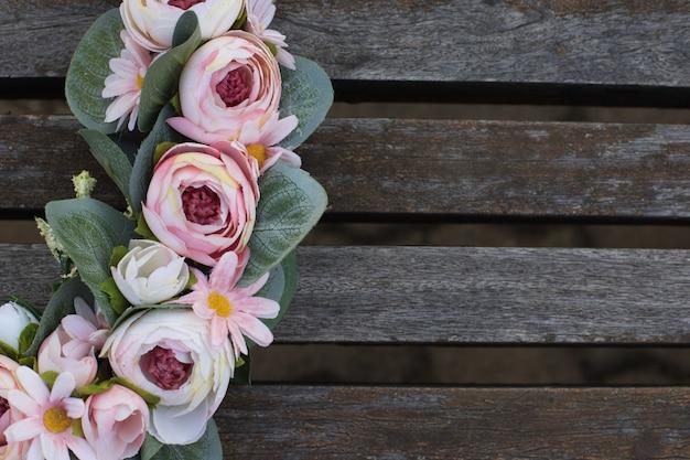 Primer plano de delicadas guirnaldas de rosas sobre fondo de madera