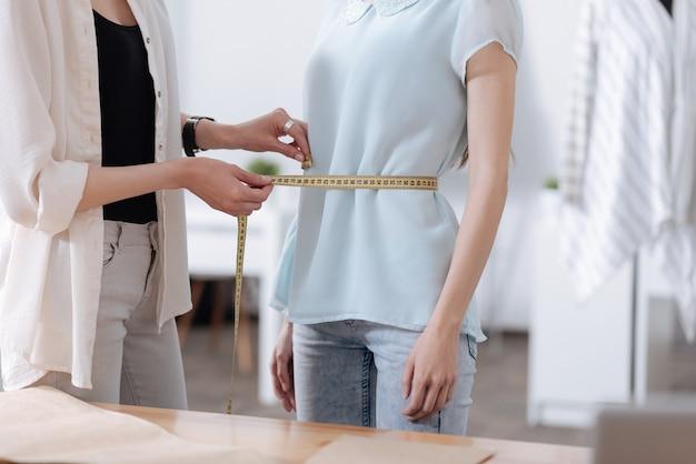 Un primer plano de delicadas manos femeninas que miden la delgada cintura de su amiga en buena forma
