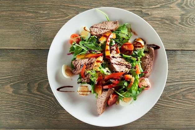 Primer plano de deliciosa ensalada de verduras, incluidas rodajas de ternera, huevos de codorniz, tomates cherry. delicioso para comidas de restaurante con vino tinto claro o blanco o champán