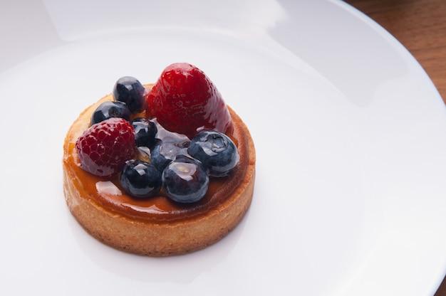 Primer plano de deliciosa mini tarta con bayas en placa