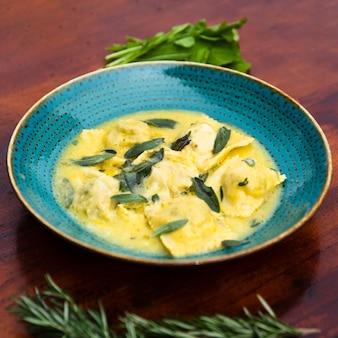 Primer plano de deliciosa pasta de ravioles decorar con hojas de albahaca sobre mesa de madera