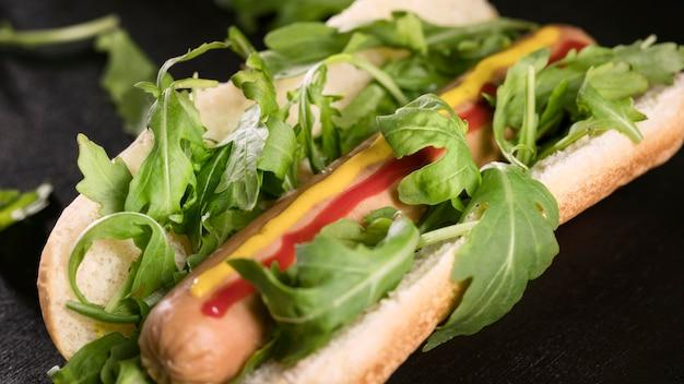 Primer plano delicioso hot dog con hojas comestibles