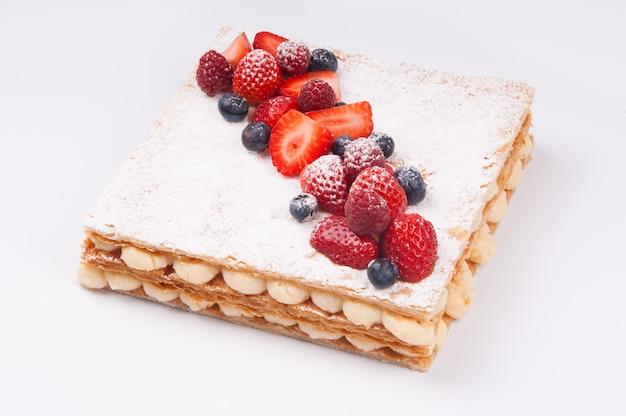 Primer plano de un delicioso pastel de bayas con azúcar en polvo en la capa superior