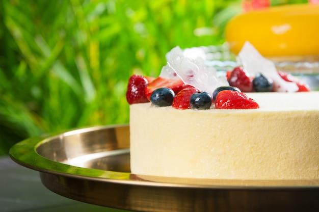 Primer plano de delicioso pastel de queso con bayas en bandeja al aire libre