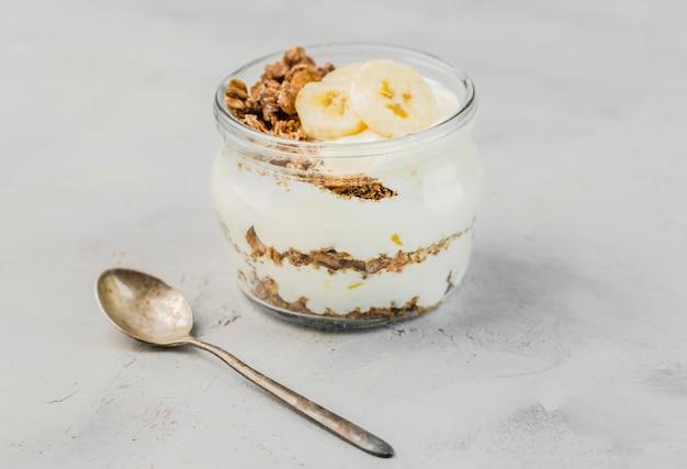 Primer plano delicioso yogurt con granola y plátano