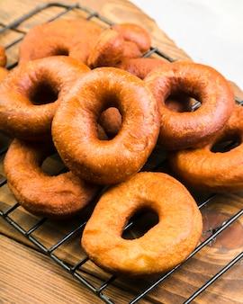 Primer plano de deliciosos donuts marrones en bandeja metálica sobre mostrador