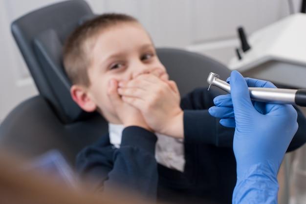 Primer plano de dentista en guantes con broca dental en mano y niño asustado por dentistas