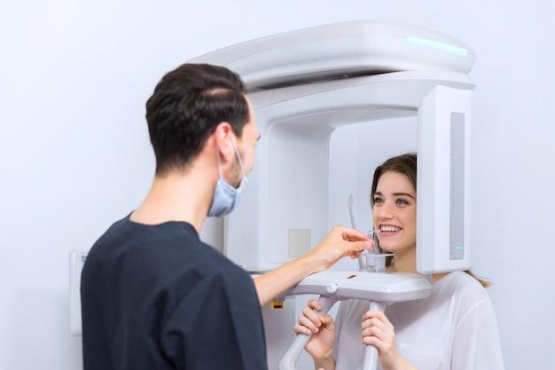Primer plano de dentista masculino mirando paciente femenino en máquina de rayos x