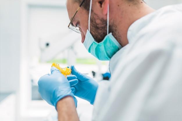 Primer plano de un dentista mirando la impresión dental en la clínica
