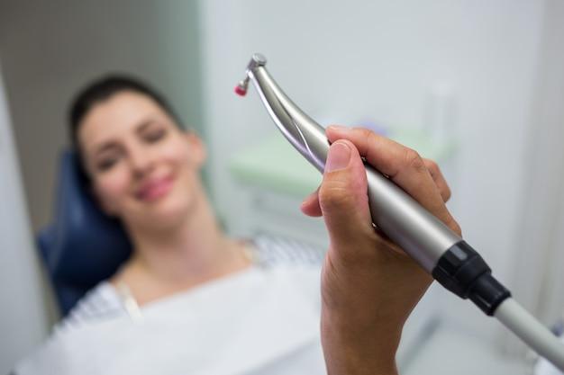 Primer plano del dentista sosteniendo una odontología, pieza de mano dental mientras examina a una mujer